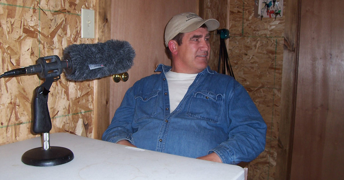 A man in a blue button down shirt and baseball cap sits at a desk in a wood paneled room with a microphone in front of him.
