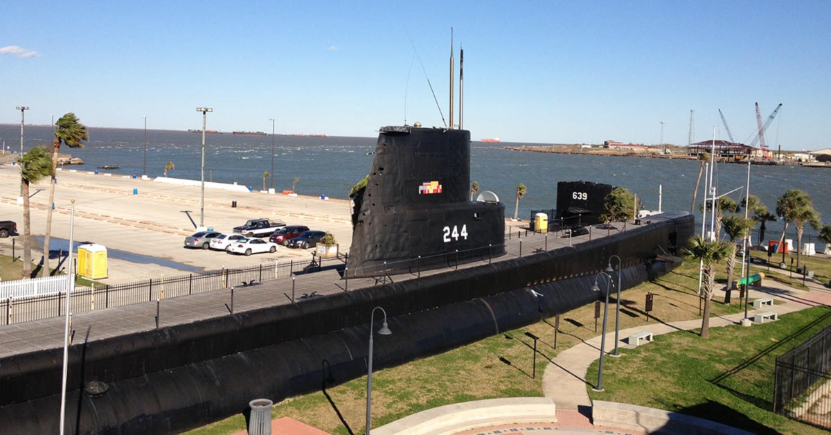 A long black submarine sits on land with it's conning tower reaching up to a blue sky. In the background are the waters of Galveston Bay.