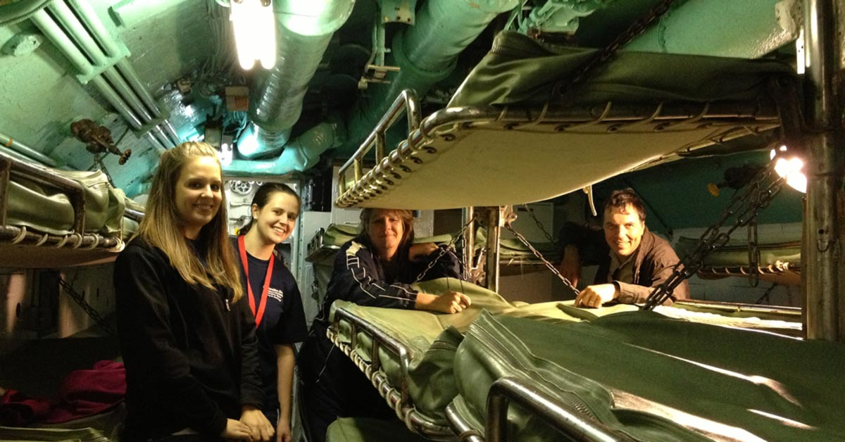 Four smiling people look to the camera in a crowded room with equipment and bunks throughout.