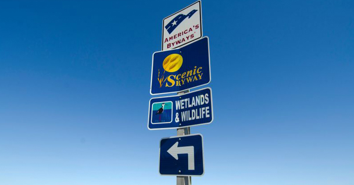 A close up of a road sigh with multiple signs with a cloudless blue sky in the background. The sign lets the viewer know they are on the Wetlands and Wildlife Scenic Byway and America's Byway System.