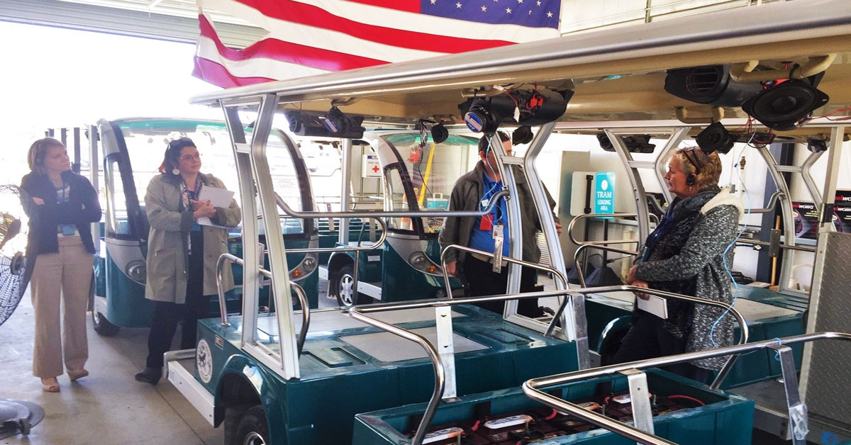 People stand around a blue tram inside a large garage with a prominent American flag.