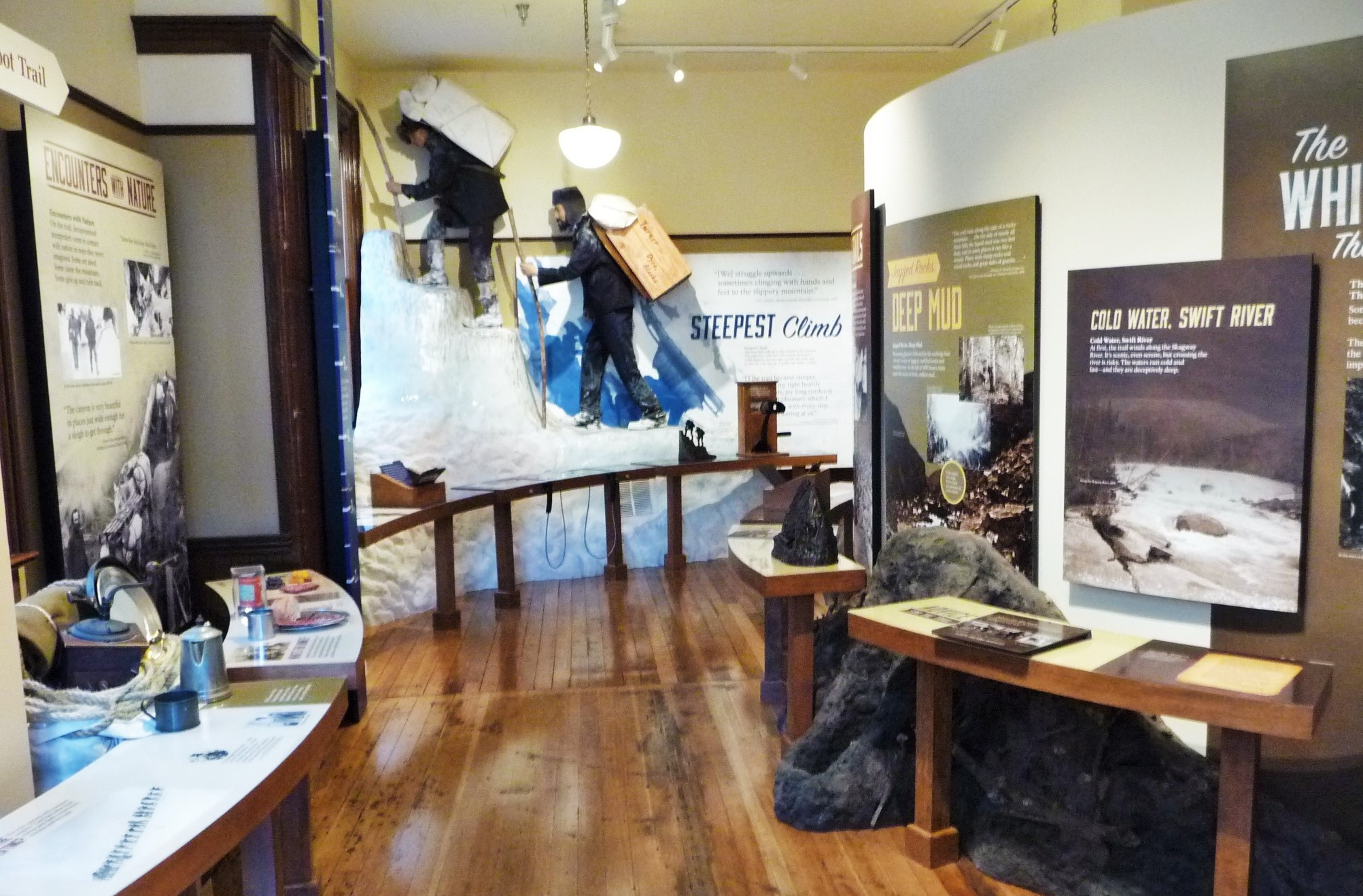 A hallway of exhibits which are located on both sides. At the end is a diorama with two hikers in turn of the 20th century cold-weather hiking gear.