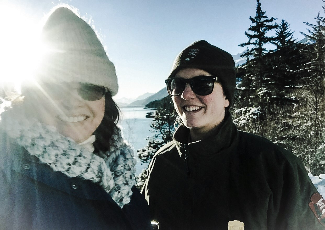 Two women in heavy winter coats and sunglasses smile at the camera with mountains and a lake in the distance.