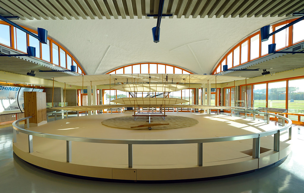 A wooden and fabric biplane sits in a large curved hall with floor to ceiling windows. Around the model is a waist-high railing which has informational panels attached.
