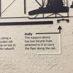 A close-up of a information panel showing a graphic of the dolly used under the Flyer to run it down the launch rail with the Braille translation underneath.